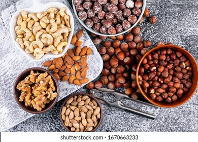 Flat lay almonds, hazelnuts, different nuts in brown and white bowls with nutcracker and pecan, pistachios, almond on dark stone textured and white cutting board background. horizontal