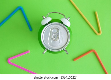 Flat lay of aluminum can in form of alarm clock and colorful drinking straws minimal beverage and recycle creative concepts.