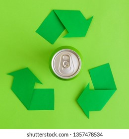 Flat lay of aluminum can and recycle symbol arrows minimal eco friendly creative concept.