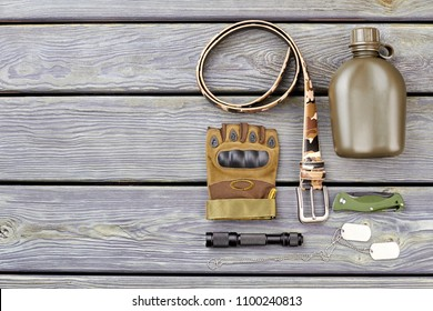 Flat Lay of army soldier necessities. camp combat accessoires on wood.
