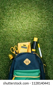 flat lay with arranged backpack and stationery on green grass