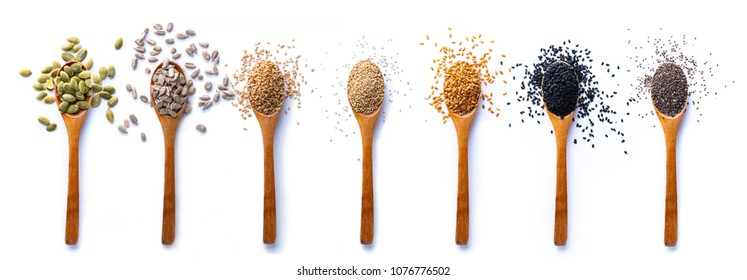 Flat lay of arranged wooden spoons with various healthy seeds in mix on white background.