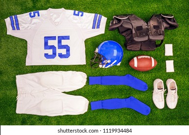 A flat lay arrangement of an Americam Football kit with ball, shirt, helmet and protective pads.