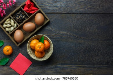 Flat lay of arrangement Chinese new year & lunar background holiday concept. Orange and essential food on modern rustic wooden at home office desk.Free space for creative design text and wording.