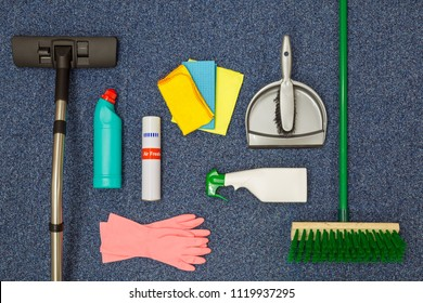 A flat lay arrangement of cleaning equipment on a blue office carpat background.