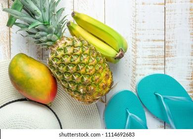 ba4e397465e Flat Lay Arrangement Composition Tropical Fruits Pineapple Mango Bananas  Women Hat Blue Slippers on White Planked