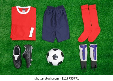 A flat lay arrangement of football or soccer kit on grass, with shirt, shorts,socks, boots, shin pads and ball.