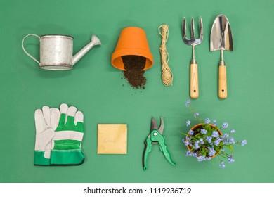 A flat lay arrangement of Gardening equipment on a green background
