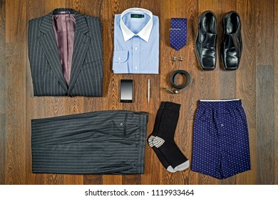 A flat lay arrangement of mens business attire with grey pin striped suit, white collar shirt, black shoes and matching accessories.