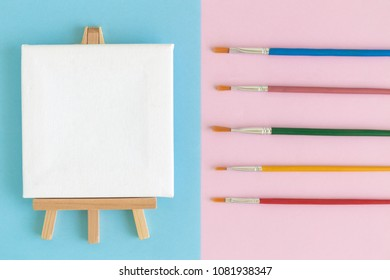 Flat lay of art canvas on easel and colorful paintbrushes on blue and pink background minimal creative concept
