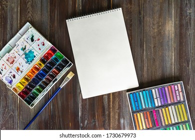 Flat lay art workplace, wooden table with paint brushes, watercolor paints, paper canva and crayon pastel chalks