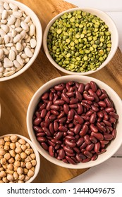 Flat lay of assortment of peas, lentils, beans and legumes over white wooden background.