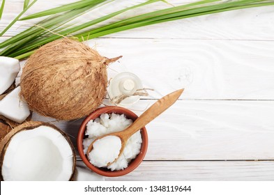 Flat lay Background of coconut, coconut shell, oil in clay bowl and glass jar and spoon on white wooden table