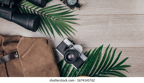 Flat lay of backpack, camera, binoculars and compass on wooden background wih palm tree leaves. Travel equipment for outdoor advenure.