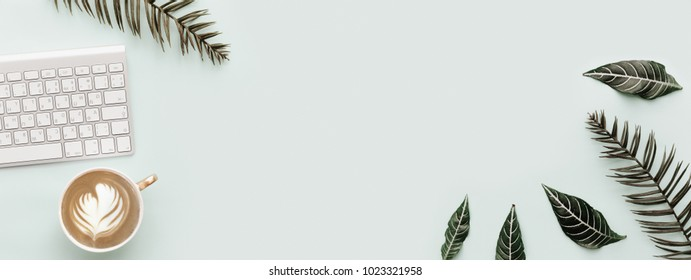 Flat Lay Banner, Simple Trendy Office Desk with keyboard and botanical tropical elements. Minimal Modern Hipster Composition