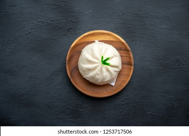 Flat lay Baozi or bao dim sum on plate with copy space on dark background.