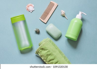 Flat lay bath products, cosmetic for shower. Shampoo or shower gel, soap bar, cotton towel, wooden comb and seashells. Top view photo natural cosmetics
