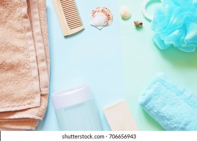 Flat lay bath products. Frame, border for design beauty blog and web site. Terry towel, comb, shampoo bottle, soap and sponge puff on a blue background. Top view stock photo. Shower items