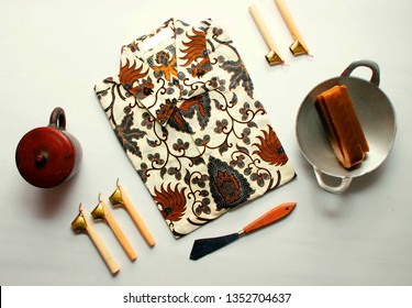 flat lay batik clotes with canting, small pan and wax earthenware glass isolated on white background