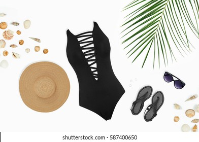 Flat lay beach accessories: swimsuit, sunglasses, hat, sandals with palm branches and shells. Top view on white background