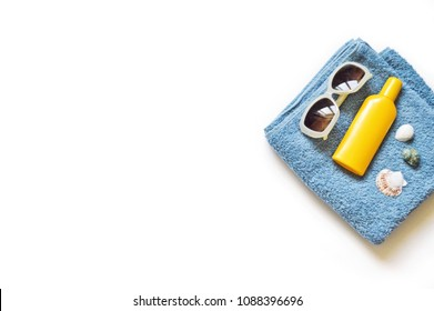 Flat lay beach photo. Blue cotton towel, brown sunglasses, yellow sunscreen bottle and seashells on a white background. Summer season, sea travel, beach holiday concept