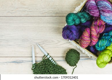 Flat lay of beautiful skeins and needles in purple and green tones inside a basket over a wooden table