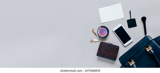 Flat lay of black leather woman bag open out with cosmetics, accessories, wallet, smartphone and card of paper on grey background with copy space, banner style for text