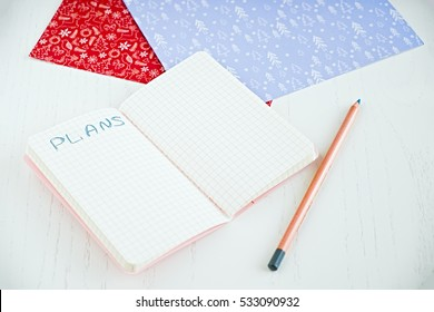 Flat lay of blank notepad for make plans, pencil, decorated Christmas papers. on a white table. Perspective view. New year resolution planning