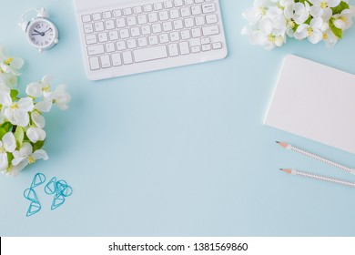 Flat lay blogger or freelancer workspace with a notebook, keyboard and white spring flowers on a blue background