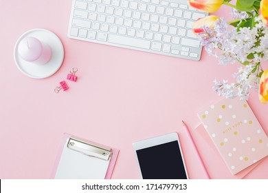 Flat lay blogger or freelancer workspace with a keyboard, yellow tulips and branches of lilac, office supplies on a pink background