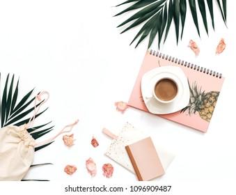 Flaches Bloggerarbeitsplatz mit tropischen Blättern, Kaffee und Accessoires auf weißem Hintergrund. Leerzeichen kopieren