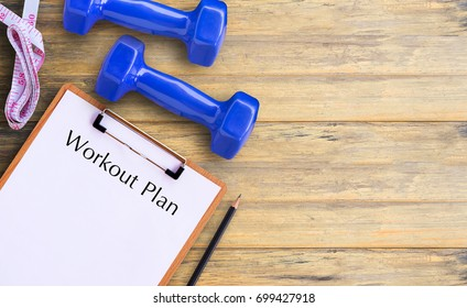 Flat lay - Blue dumbbell, Measuring Tape, Pencil and health clipboard indicating workout plan on wooden table. Top view with copy space for any design. Healthy and fitness concept.