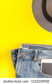 Flat lay of blue jeans, grey hat and smartphone headphones on bold yellow paper background with copy space. Overhead view of woman casual outfit. Trendy hipster look top view
