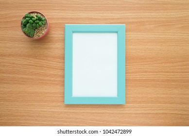 Flat lay of blue photo frame and cactus mockup on wooden table for creative design concept