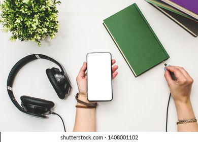 Flat lay. Books and headphones connected to them on a white background. Smart phone. Concept Audiobooks