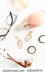 Flat lay of bottles of perfume, golden earrings, glasses and cotton branch on white desk