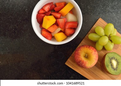 Flat lay of a bowl with Fruit salad on a granite countertop
