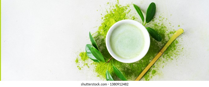 Flat lay of bowl organic green tea Matcha powder with Chashaku spoon  on light background with copy space. Long wide banner.
