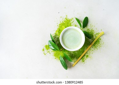Flat lay of bowl organic green tea Matcha powder with Chashaku spoon  on light background with copy space.