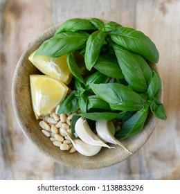 Flat lay bowl of pesto ingredients including fresh basil, lemons, garlic and pine nuts.