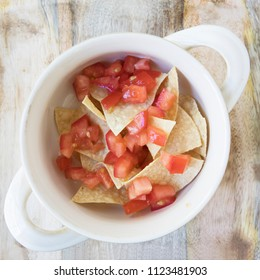 Flat lay of  bowl  with tortilla chips and tomatoes, ready for filling with soup. (third of five in series)