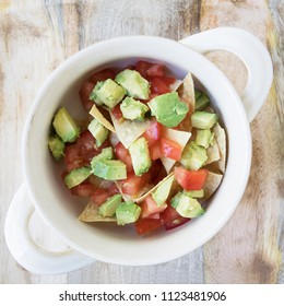 Flat lay of  bowl  with tortilla chips, tomatoes, and avocados,  ready for filling with soup. (fourth of five in series)