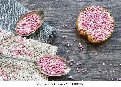 flat lay breakfast scene with two vintage silver spoon with typical Dutch food muisjes, pink and white aniseed, for announcement birth of a daughter, baby girl
