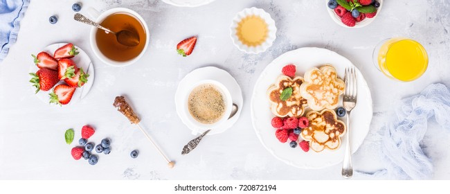 Flat lay with breakfast with scotch pancakes in flower form, berries and honey on light wooden table. Healthy food concept. Banner.