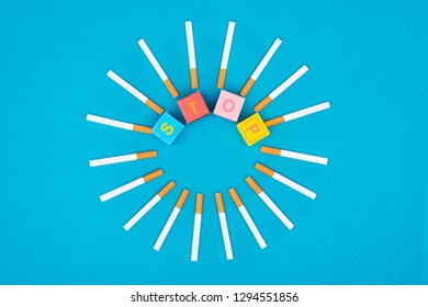 Flat lay with bright letter cubes and cigarettes isolated on blue, stop smoking concept