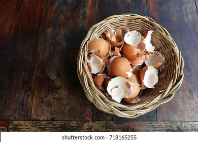 Flat lay of broken egg shell in wood basket on wood table, reusing eggshell for many purposes and reducing the waste from kitchen and global warming effect