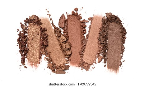 Flat lay of brush stroke. Broken shiny brown or bronze color eyeshadow as sample of cosmetic beauty product isolated on white background