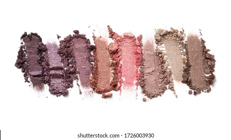Flat lay of brush strokes. Broken multicolor eyeshadow as samples of cosmetic beauty product isolated on white background
