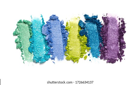 Flat lay of brush strokes. Broken bright multicolor eyeshadow as samples of cosmetic beauty product isolated on white background