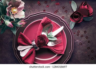 Flat lay with burgindy plates and crockery decorated with roses and anemones, Christmas or Valentine dinner table setup